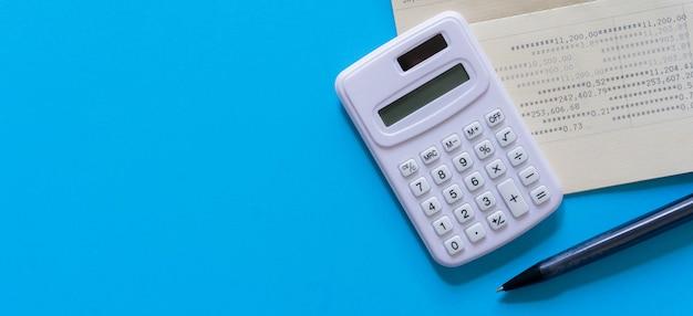 Calcolatrice con libretto di conto bancario e matita su sfondo di colore blu