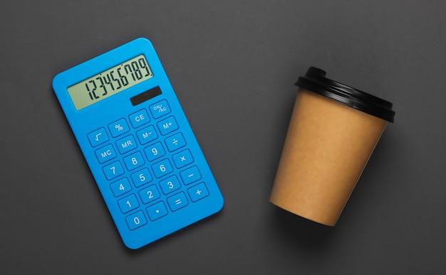 Calcolatrice con una tazza di caffè di cartone su grigio