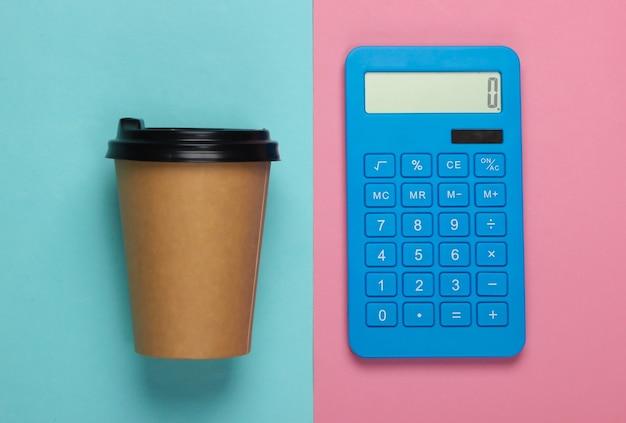 Calcolatrice con una tazza di caffè di cartone su pastello blu rosa