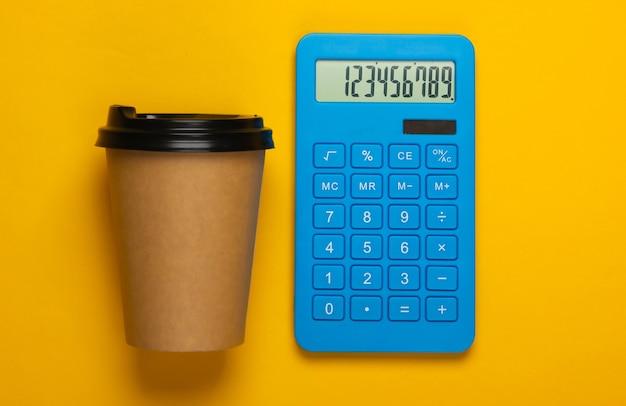 Calcolatrice con una tazza di caffè di cartone su giallo