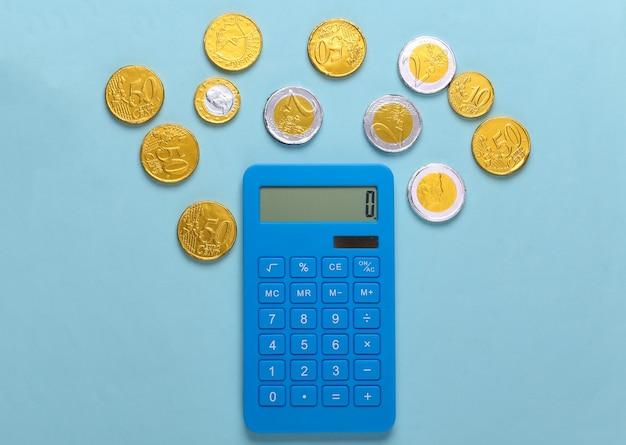 Calcolatrice con monete su blu
