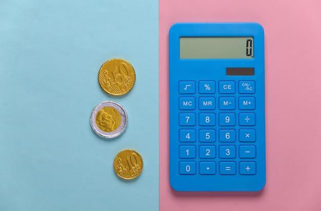 Calcolatrice con monete su pastello blu rosa