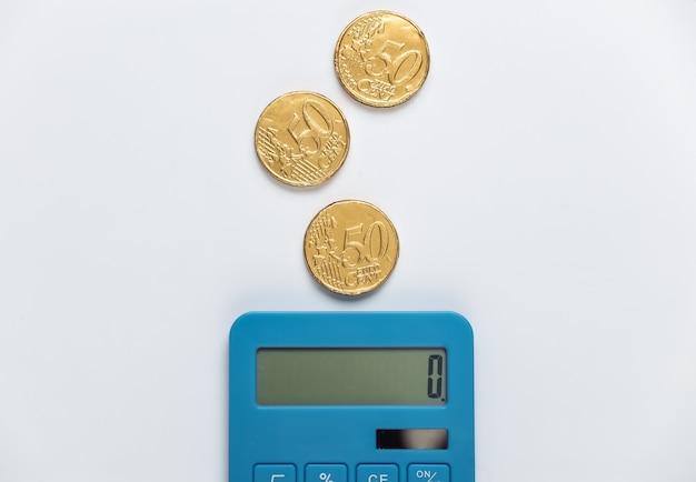 Calcolatrice con monete su bianco