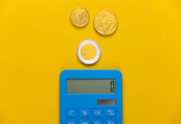 Calcolatrice con monete su giallo