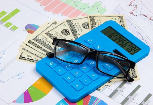 Calcolatrice con banconote da un dollaro, grafici e grafici, bicchieri. calcolo economico, costi.