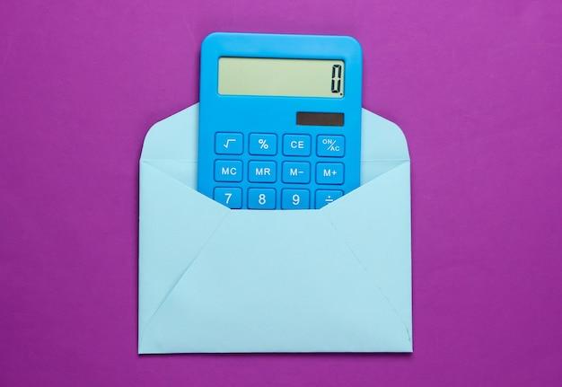 Calcolatrice con una busta su una viola