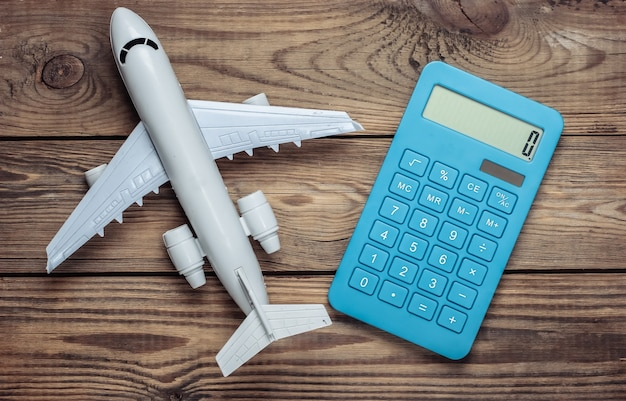 Calcolatrice con la figura di un aeroplano su un tavolo di legno. calcolo del costo del viaggio aereo