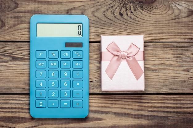 Calcolatrice con una confezione regalo su un legno