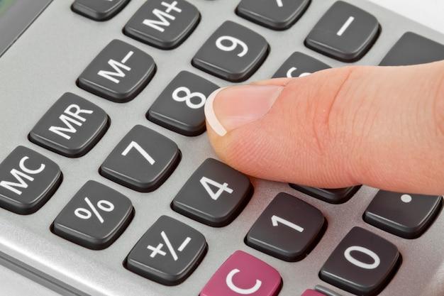 Calcolatrice con mano isolata su bianco