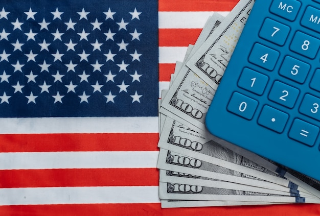 Calcolatrice con banconote da cento dollari sulla bandiera degli stati uniti