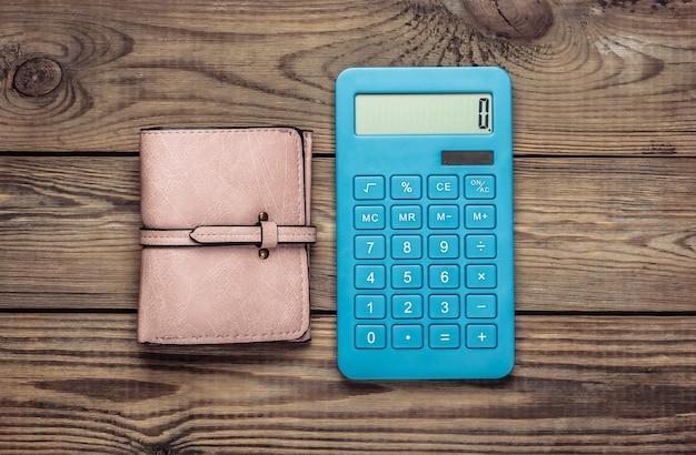 Calcolatrice con portafoglio in pelle sulla tavola di legno