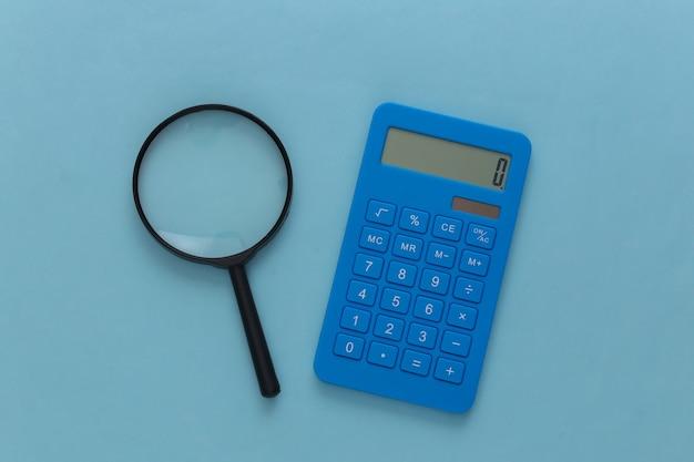 Calcolatrice con una lente d'ingrandimento su un blu