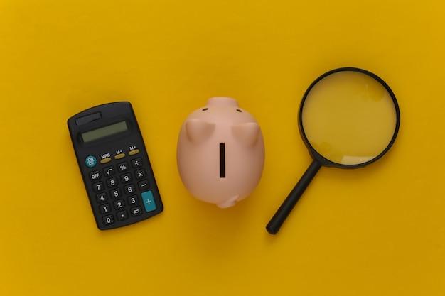 Calcolatrice con lente d'ingrandimento e salvadanaio su giallo