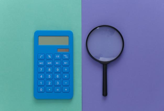 Calcolatrice con una lente d'ingrandimento su viola blu