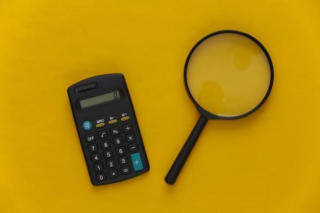 Calcolatrice con una lente d'ingrandimento su giallo