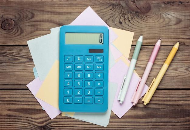 Calcolatrice con fogli di appunti e penne colorate su un tavolo di legno.