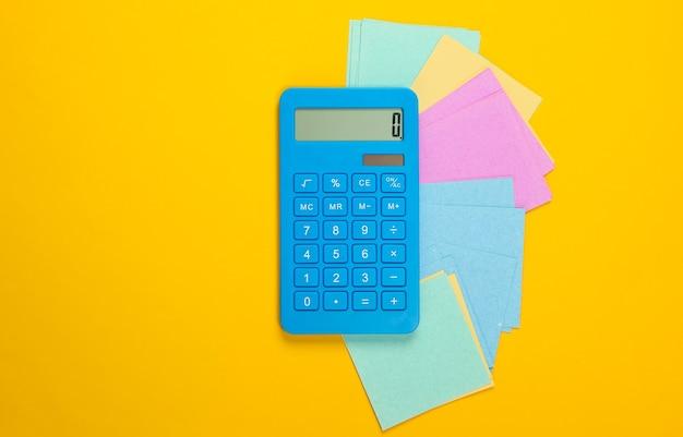 Calcolatrice con pezzi di carta memo su un giallo
