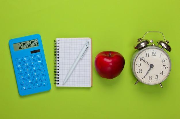 Calcolatrice con taccuino, mela, sveglia sul verde. di nuovo a scuola. concetto di educazione