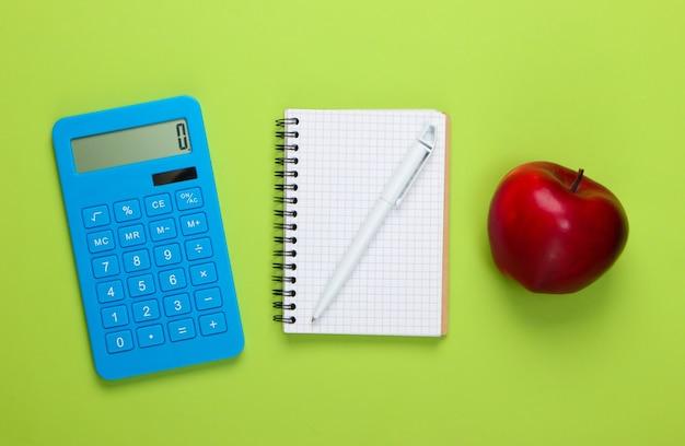 Calcolatrice con il taccuino, mela sul verde. di nuovo a scuola. concetto di educazione
