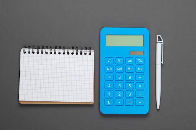 Calcolatrice con un taccuino su un grigio. gestione del bilancio familiare.