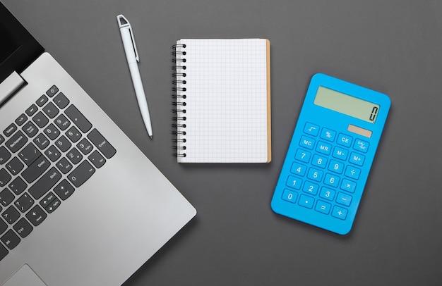 Calcolatrice con notebook e laptop su grigio. gestione del bilancio familiare