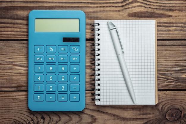 Calcolatrice con il taccuino su un legno