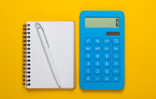 Calcolatrice con notebook su sfondo giallo. processo educativo. vista dall'alto. lay piatto