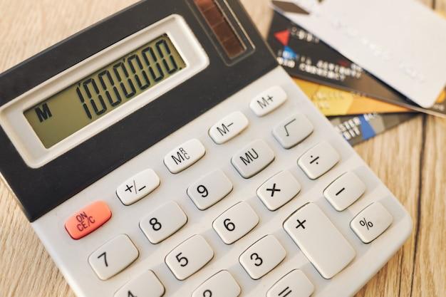 Calcolatrice con un milione, carte di credito sul tavolo di legno