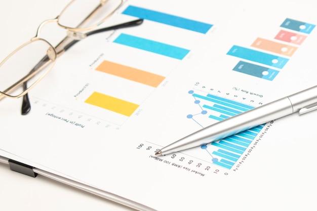 Calcolatrice con penna su dati finanziari. concetto di ricerca aziendale e finanziaria.