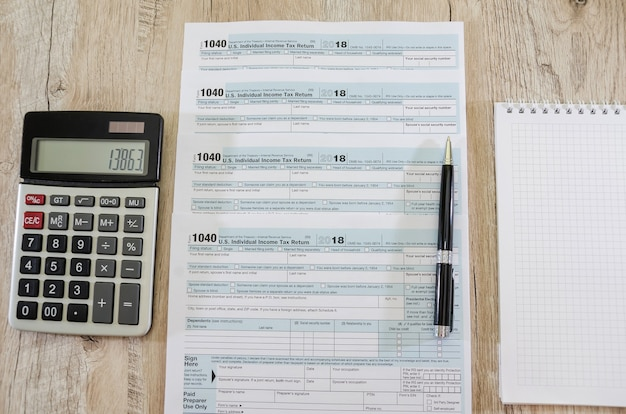 Calcolatrice con penna e moduli fiscali 1040 su sfondo di legno