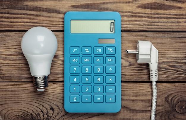 Calcolatrice con una spina di alimentazione, lampadina su legno. calcolo dei costi di consumo energetico