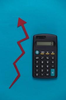 Calcolatrice con freccia di crescita rossa sull'azzurro. grafico a freccia che sale. la crescita economica