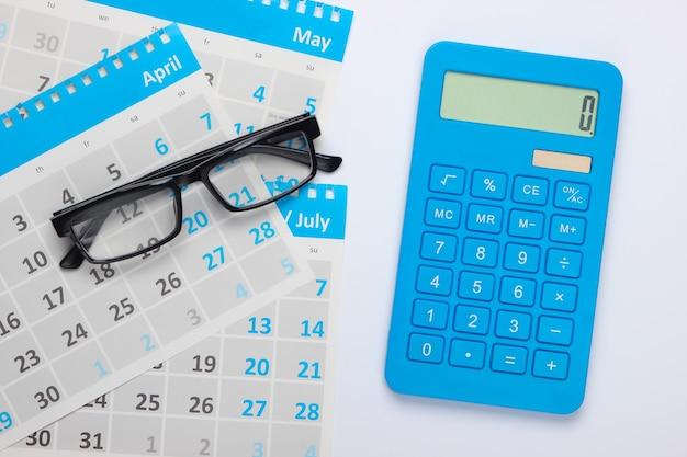 Calcolatrice con fogli del calendario mensile, bicchieri su bianco