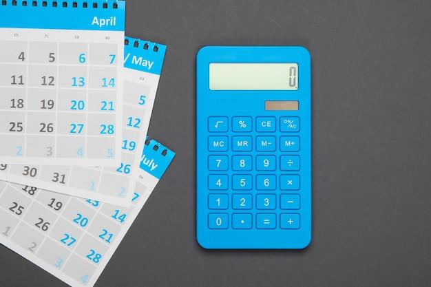 Calcolatrice con i fogli del calendario mensile in grigio. calcolo dei canoni di locazione per gli alloggi.