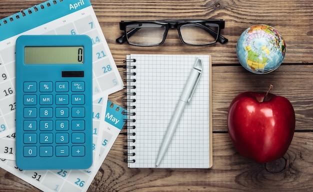 Calcolatrice con i fogli del calendario mensile, taccuino, mela, globo su legno