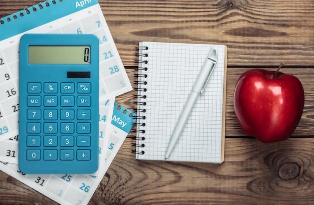 Calcolatrice con i fogli del calendario mensile, taccuino, mela su legno