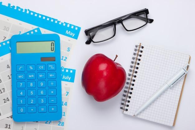 Calcolatrice con fogli di calendario mensile, taccuino, mela rossa, bicchieri su bianco. calcolo economico, costi