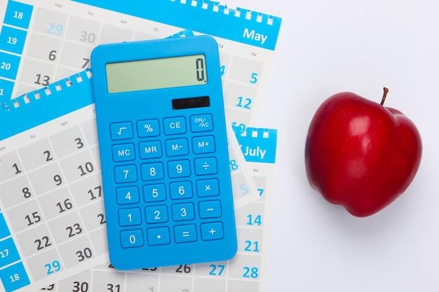 Calcolatrice con i fogli del calendario mensile, mela rossa su fondo bianco. calcolo economico, costi