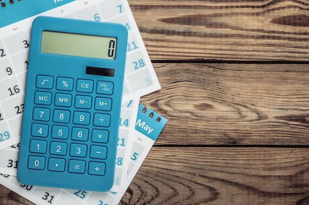 Calcolatrice con i fogli del calendario mensile su legno