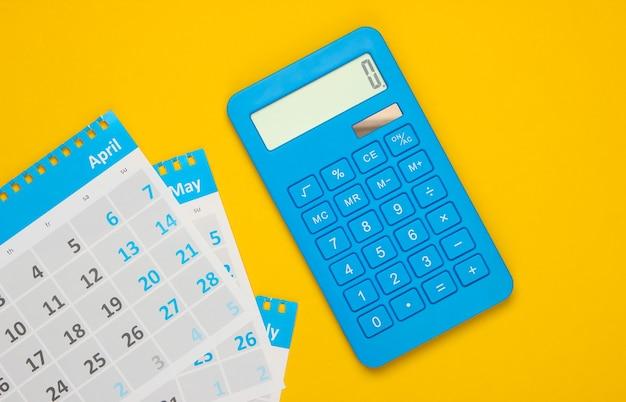Calcolatrice con i fogli del calendario mensile in giallo. calcolo dei canoni di locazione per gli alloggi