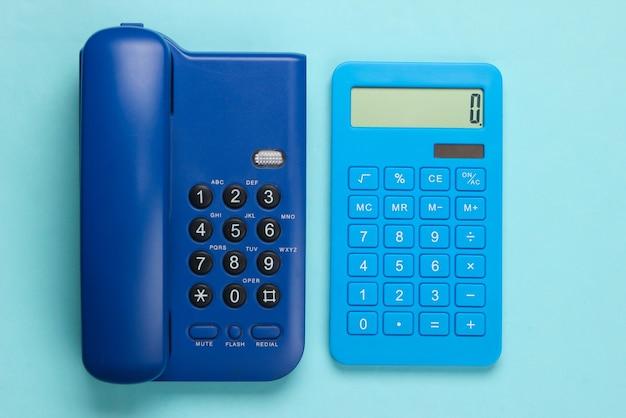Calcolatrice con un telefono fisso dell'ufficio su un blu.