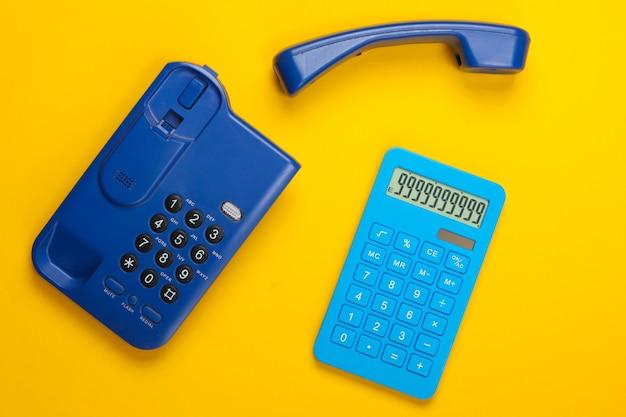 Calcolatrice con un telefono fisso dell'ufficio su colore giallo