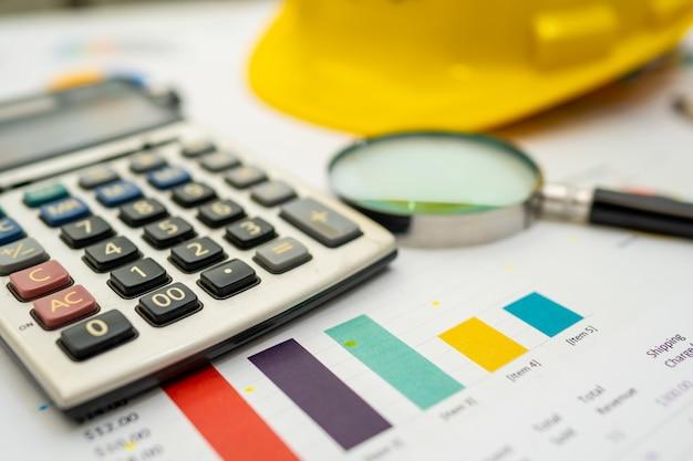 Calcolatrice con casco costruzione gialla su carta millimetrata.