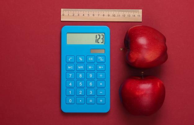 Calcolatrice e righello di legno e mela sul rosso. concetto di educazione