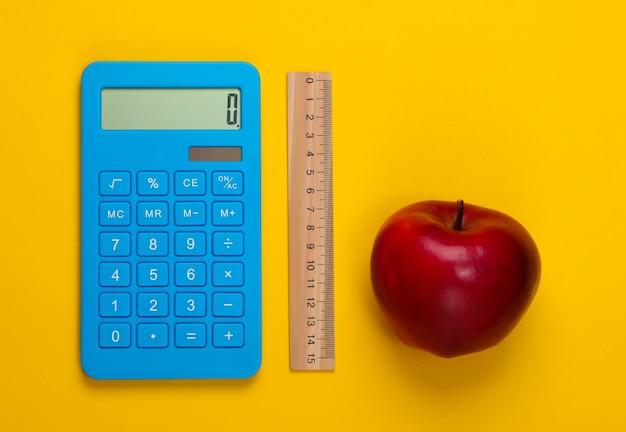 Calcolatrice e righello di legno, mela su colore giallo. concetto di educazione