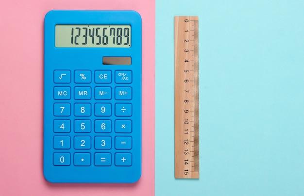 Calcolatrice e righello di legno su pastello blu rosa. concetto di educazione