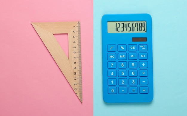 Calcolatrice e righello di legno, triangolo su un pastello bluepink. concetto di educazione
