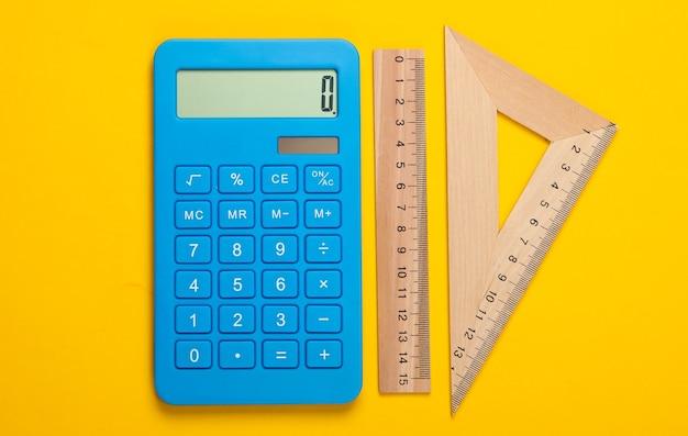 Calcolatrice e righello in legno, triangolo giallo. concetto di educazione