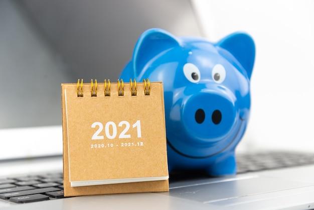 Calendario 2021 con salvadanaio blu su laptop con pavimento bianco. risparmio finanziario e concetto di ricchezza di denaro. concetto di acquisto di affari.