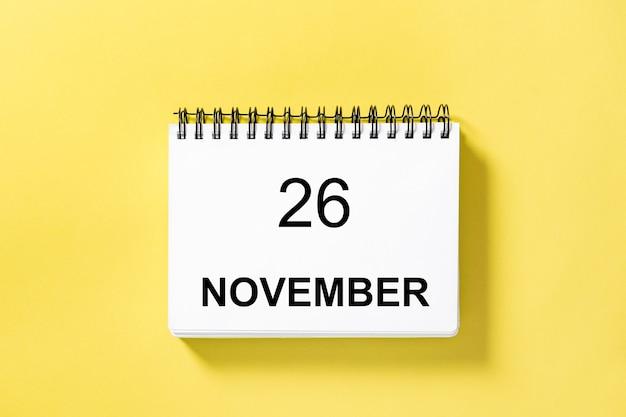 Libro del calendario per la data su sfondo giallo. 26 novembre